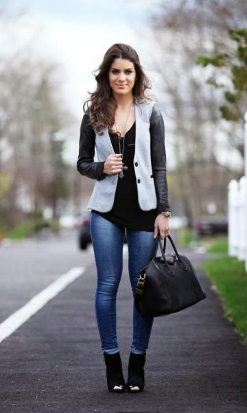 modelo usa colete cinza, calça jeans, bolsa preta e blusa na mesma cor.