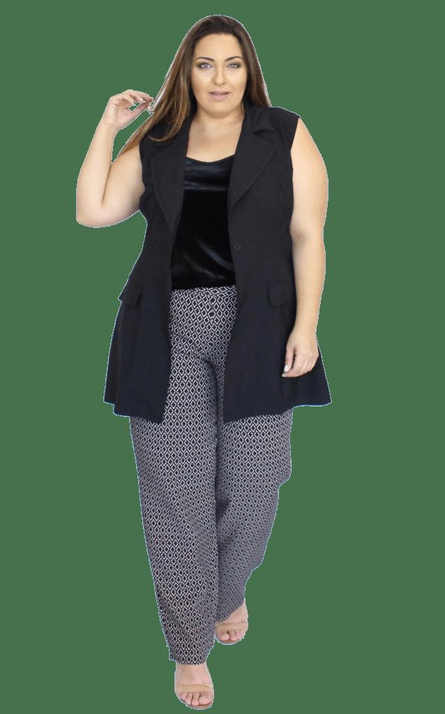modelo usa calça social, blusa e colete pretos.