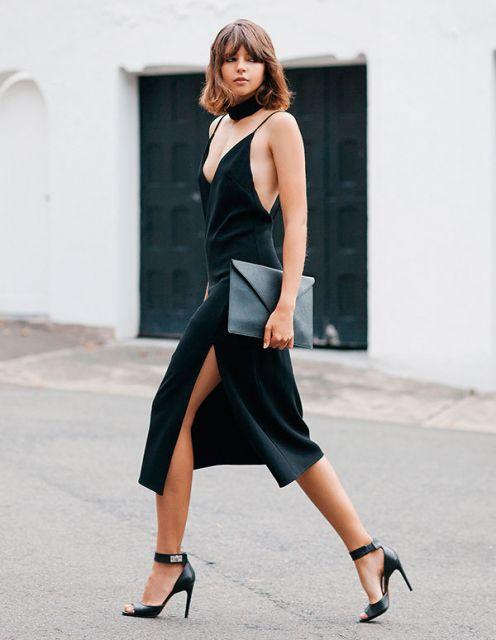 modelo usa vestido preto e carteira na mesma cor.