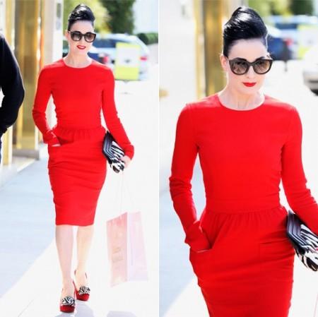 modelo usa vestido vermelho, sapato e bolsa preta.