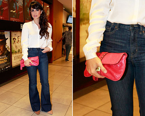 modelo usa calça jeans, com camisa e carteira vermelha.