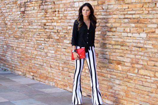 modelo usa calça flare preta e branca, camisa preta e carteira feminina vermelha.