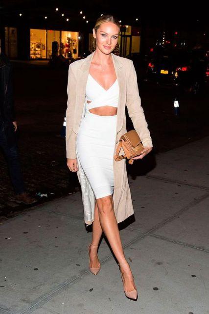 modelo usa saia, blusa branca e carteira em tons areia.