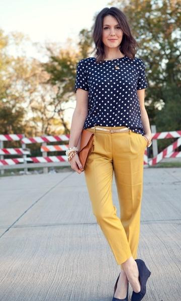 modelo usa calça amarela, camiseta azul de bolinhas brancas e sandalia na mesma cor.