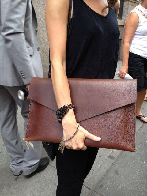 modelo usa carteira marrom estilo envelope, grande.