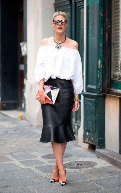modelo usa carteira feminina, saia de couro preta, blusa branca e scarpin.
