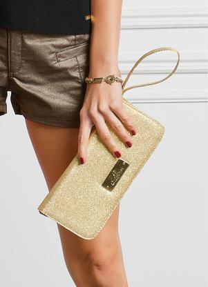 modelo usa carteira feminina dourada.