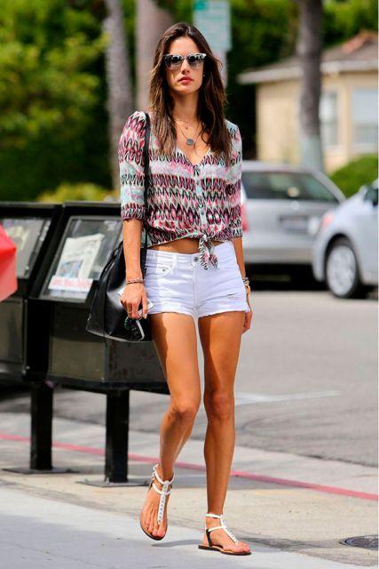 modelo usa shorts branco, camisa estampada e rasteirinha branca.