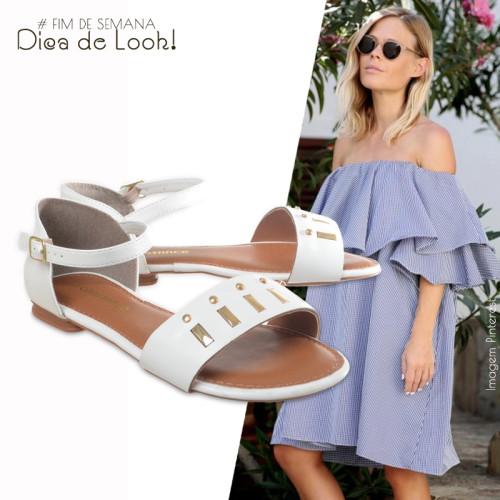 modelo usa vestido azul com rasteirinha branca.