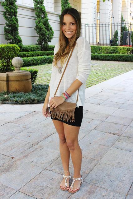 modelo usa saia preta, bolsa de franjas, sandalia, camisa branca.