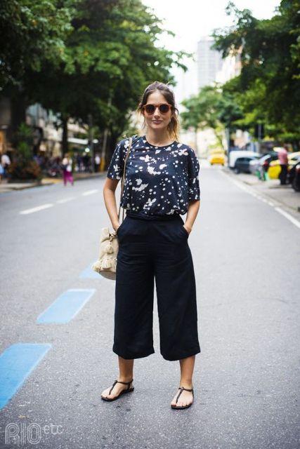 modelo usa pantacourt preta, camiseta estampada e rasteirinha preta.