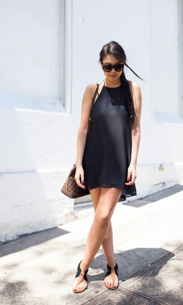 modelo veste vestido preto, sandalia preta e bolsa .
