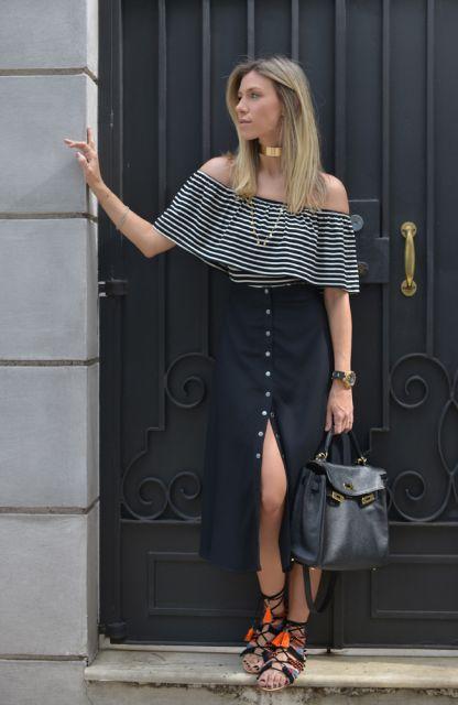 modelo veste saia preta de botao com blusa ciganinha e rasteirinha preta.