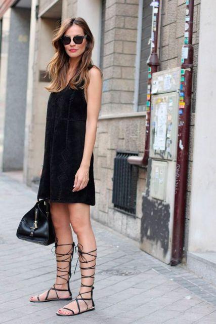 modelo usa vestido e sandalia gladiadora preta.