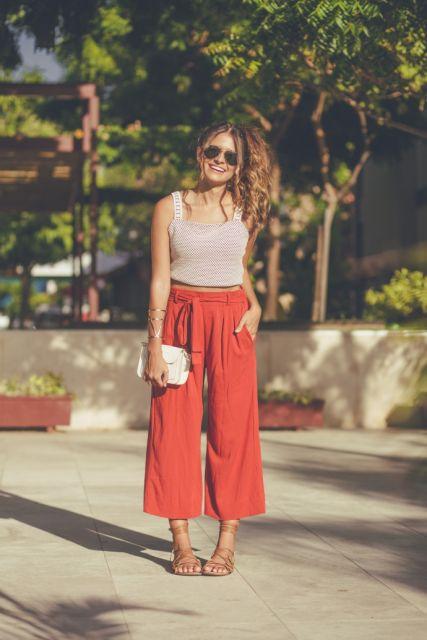 modelo veste calça pantacourt vermelha, regata e rasteirinha nude.