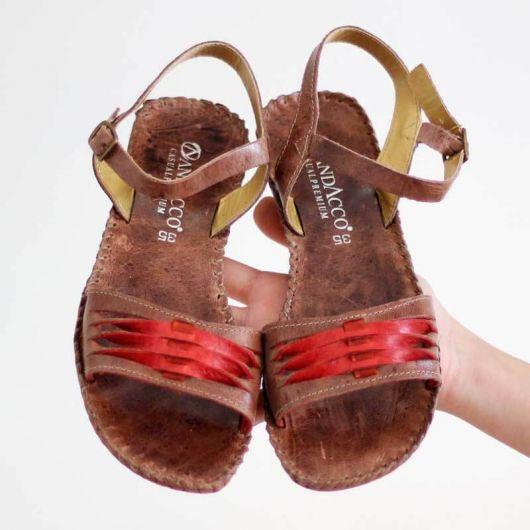 modelo de rasteirinha de couro marrom com vermelho.