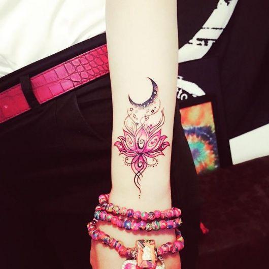 modelo com tatuagem de mandala flor de lótus cor de rosa no pulso.