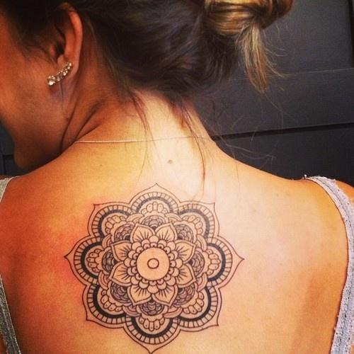 modelo com tatuagem nas costas de mandala.
