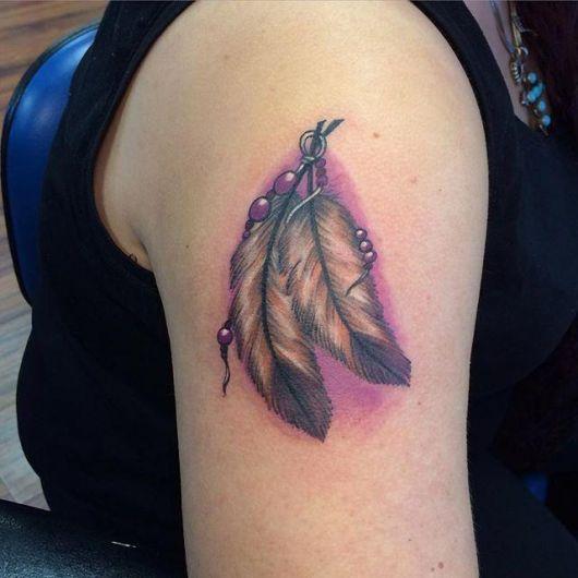 Penas sombreadas em um modelo de tatuagem indígena feminina