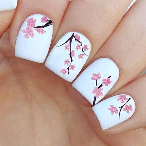 unhas brancas com flores cor de rosa e galhos marrons.