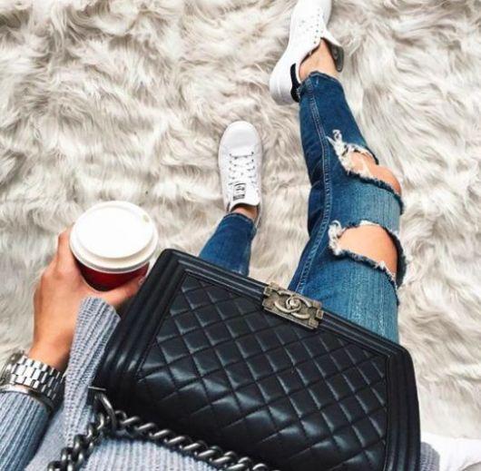 Destroyed jeans com tênis branco e bolsa com alça de corrente.