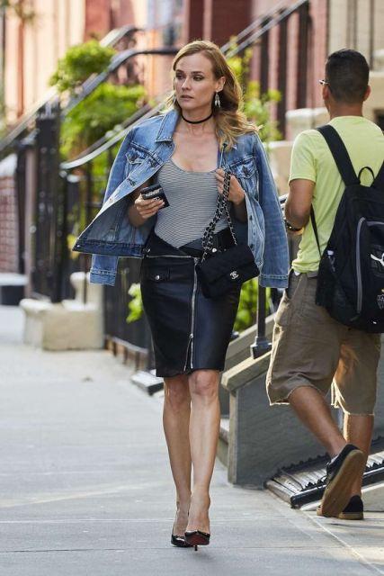 Diane Kruger usando saia de couro, body cinza, jaqueta jeans e bolsa com alça de corrente.