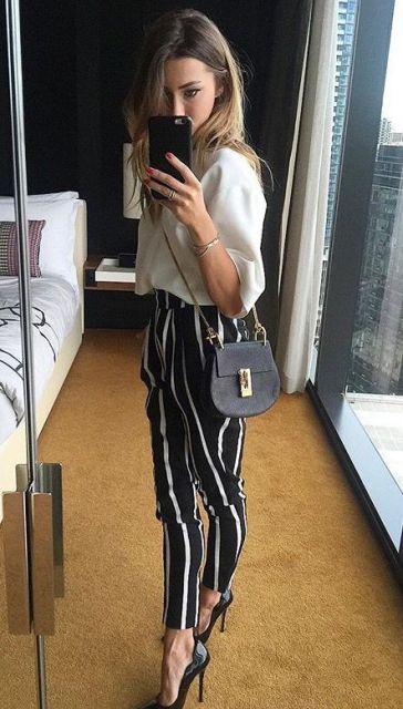 Mulher usando calça listrada e bolsa com alça de corrente.