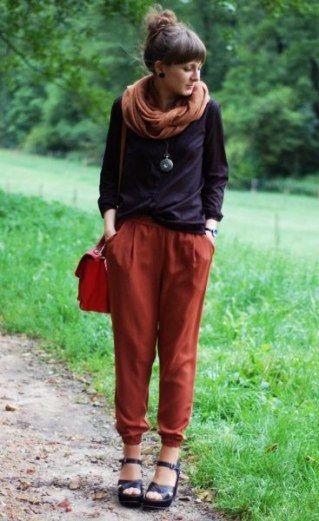 Mulher vestindo calça indiana lisa e blusa preta.