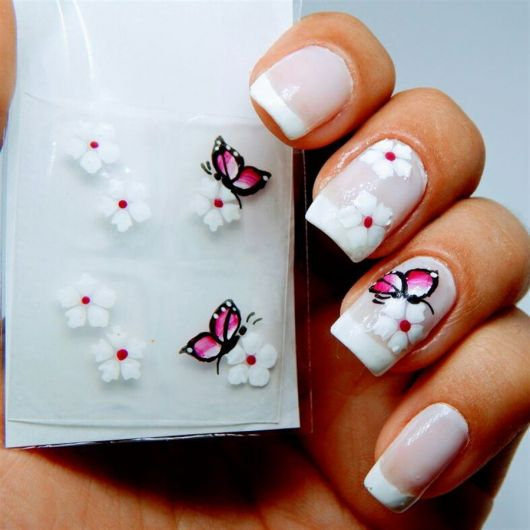 modelo com unha decoradas com borboletas brancas.