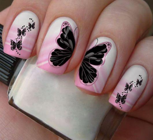 modelo com unha rosa degrade e borboletas pretas.