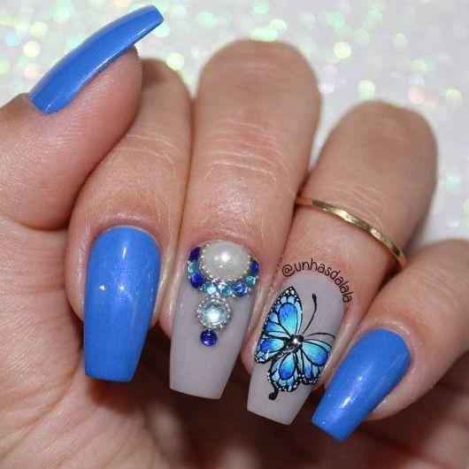 modelo usa unha azul com pedrarias delicadas.