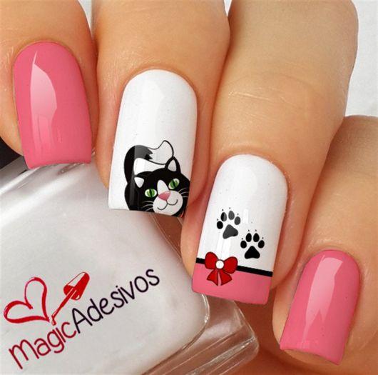 unhas branca com rosa e adesivo de gatinho preto.