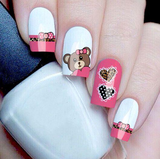unhas decoradas nas cores rosa e branco com adesivo de ursinhos.