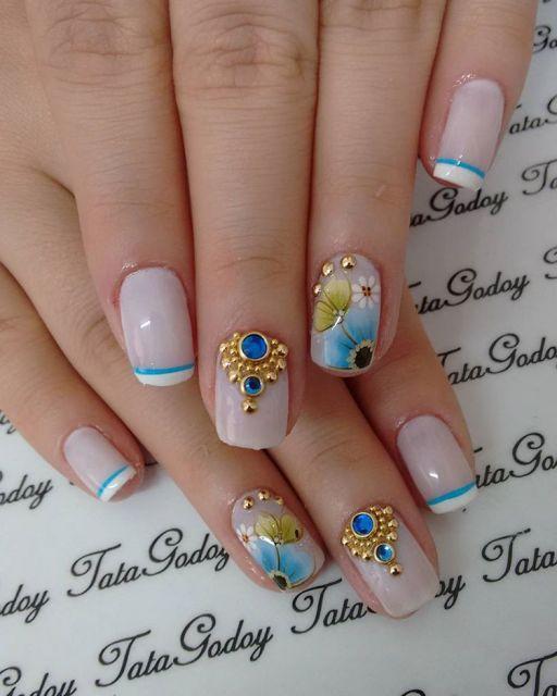 unha branca com flores e pedrarias azuis.