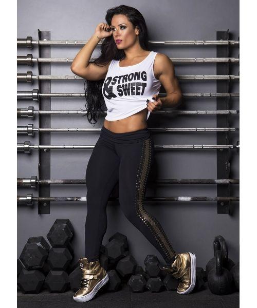modelo usa tenis dourado para academia com legging preta e camiseta branca regata.