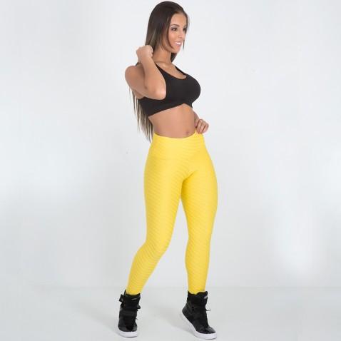 modelo usa legging amarela, tenis preto e bustie preto.