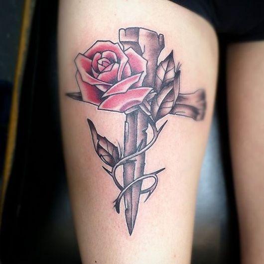Tatuagem de cruz na coxa com rosa