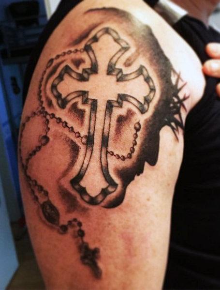 Cruz sombreada com terço e a imagem de Cristo