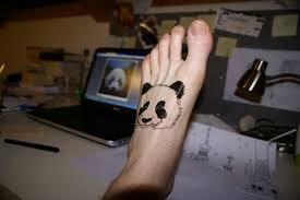 tatuagem de panda preta no pé