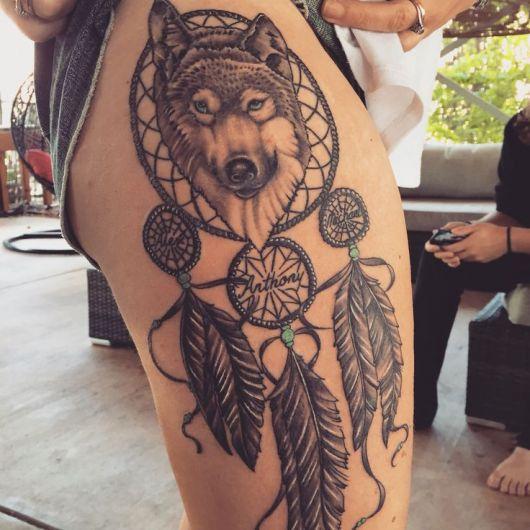 tatuagem filtro dos sonhos na coxa com rosto de lobo