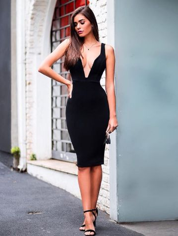 Modelo veste vestido midi preto justo com decote.