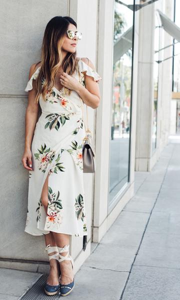 Modelo usa vestido branco com estampa floral e sandália de palha.