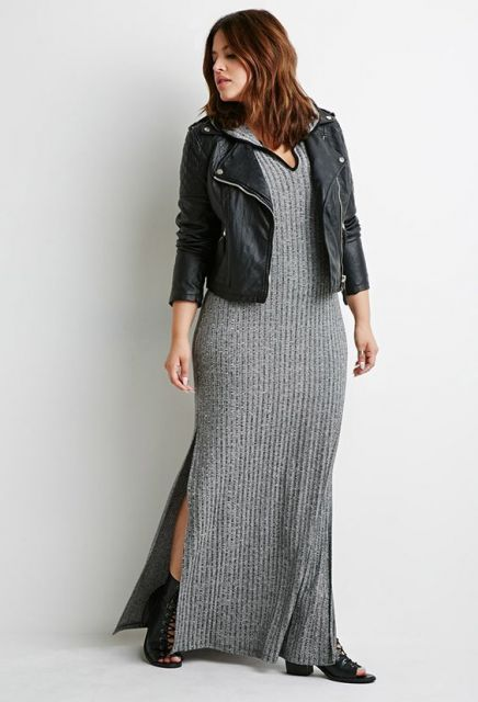 Modelo veste vestido longo cinza e jaqueta preta de couro.