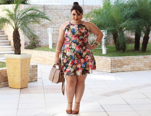 Modelo veste vestido floral curto com sandalia amarelo queimado.