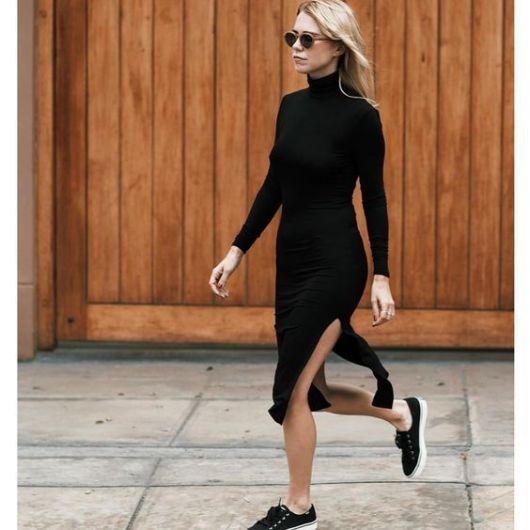 Modelo usa vestido preto com tênis.