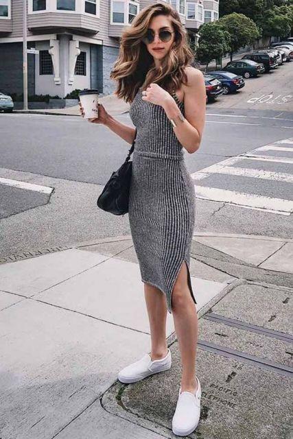 Modelo usa vestido cinza de alcinhas e tenis branco.