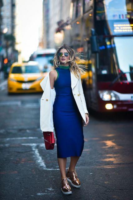 Modelo usa vestido azul escuro com jaqueta branca e tenis metalizado rosê.