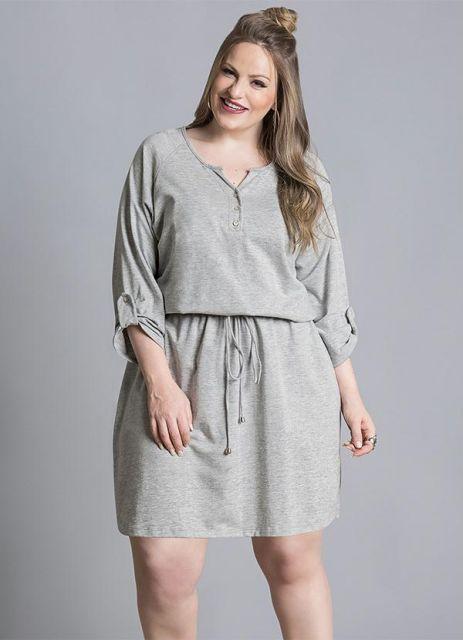 modelo usa vestido cinza curto.