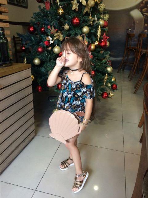 Criança usando bolsa de concha.