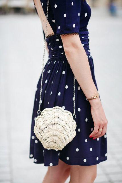 Mulher com vestido estampado e bolsa de concha.